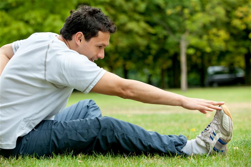 Man doing stretching exercises on the floor at the park
